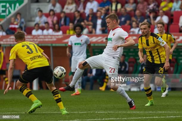 Erik Durm of Dortmund und Marcel Schmelzer of Dortmund and Alfred Finnbogason of Augsburg battle for the ball during the Bundesliga match between FC...