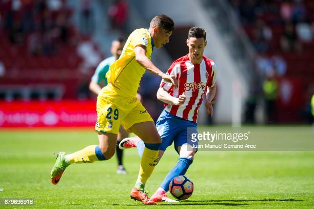 Erik Exposito of UD Las Palmas duels for the ball with Jorge Franco 'Burgui' of Real Sporting de Gijon during the La Liga match between Real Sporting...