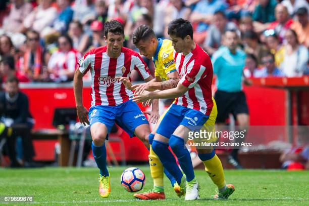 Erik Exposito of UD Las Palmas duels for the ball with Jorge Mere of Real Sporting de Gijon during the La Liga match between Real Sporting de Gijon...