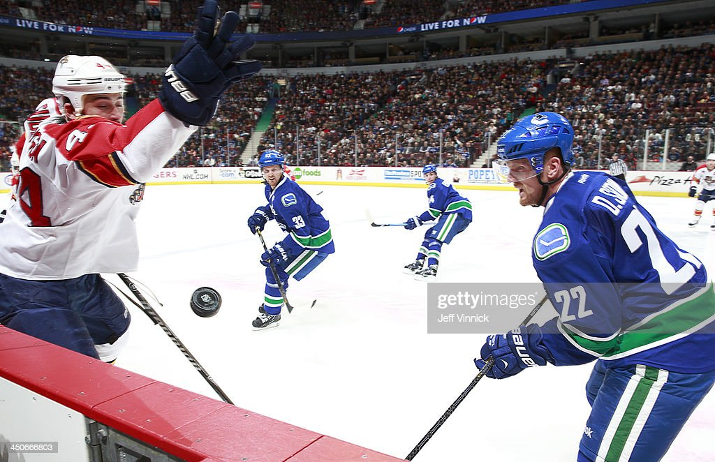 Erik Gudbranson #44 of the Florida Panthers and Daniel Sedin #22 of the Vancouver Canucks eye the puck with Henrik Sedin #33 of the Canucks in the background during their NHL game at Rogers Arena on November 19, 2013 in Vancouver, British Columbia, Canada.