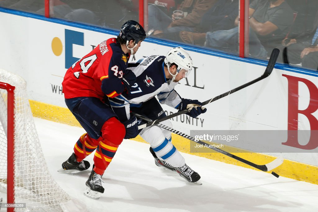 <a gi-track='captionPersonalityLinkClicked' href=/galleries/search?phrase=Erik+Gudbranson&family=editorial&specificpeople=5741800 ng-click='$event.stopPropagation()'>Erik Gudbranson</a> #44 of the Florida Panthers and <a gi-track='captionPersonalityLinkClicked' href=/galleries/search?phrase=Eric+Tangradi&family=editorial&specificpeople=4361715 ng-click='$event.stopPropagation()'>Eric Tangradi</a> #27 of the Winnipeg Jets skate after a loose puck behind the net during the third period at the BB&T Center on December 5, 2013 in Sunrise, Florida. The Panthers defeated the Jets 5-2.