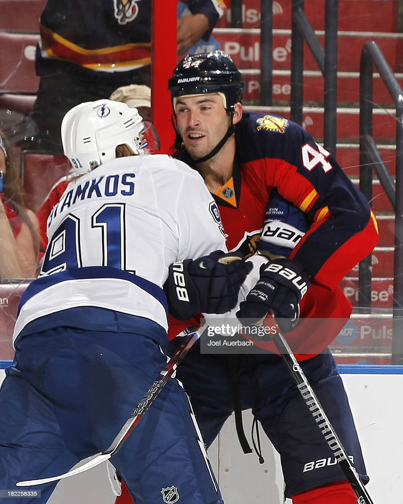 <a gi-track='captionPersonalityLinkClicked' href=/galleries/search?phrase=Erik+Gudbranson&family=editorial&specificpeople=5741800 ng-click='$event.stopPropagation()'>Erik Gudbranson</a> #44 of the Florida Panthers and <a gi-track='captionPersonalityLinkClicked' href=/galleries/search?phrase=Steven+Stamkos&family=editorial&specificpeople=4047623 ng-click='$event.stopPropagation()'>Steven Stamkos</a> #91 of the Tampa Bay Lightning come together along the boards during second period action at the BB&T Center on September 28, 2013 in Sunrise, Florida.