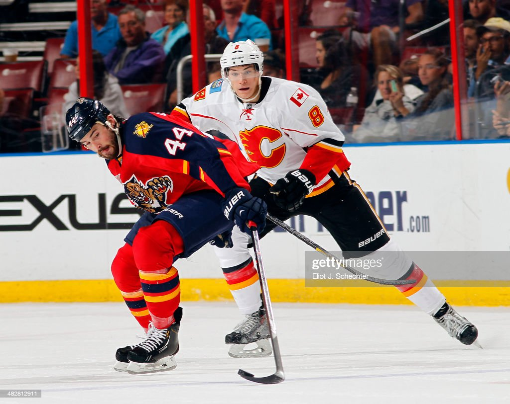 Erik Gudbranson #44 of the Florida Panthers crosses sticks with Joe Colborne #8 of the Calgary Flames at the BB&T Center on April 4, 2014 in Sunrise, Florida.