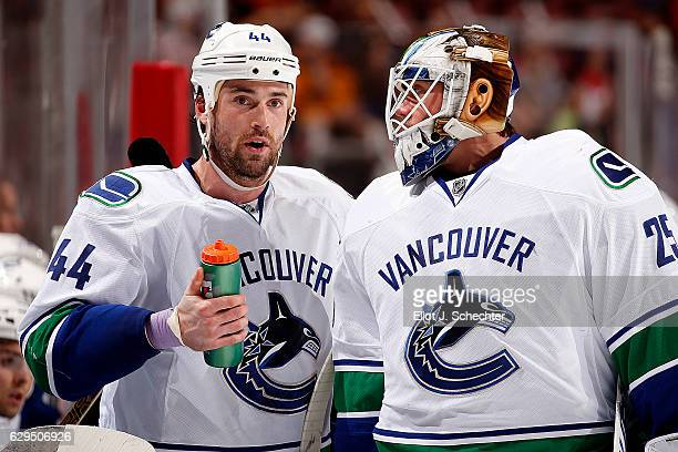 Erik Gudbranson of the Vancouver Canucks chats with teammate Goaltender Jacob Markstrom during a break in the action against the Florida Panthers at...