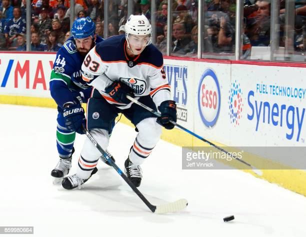 Erik Gudbranson of the Vancouver Canucks checks Ryan NugentHopkins of the Edmonton Oilers during their NHL game at Rogers Arena October 7 2017 in...
