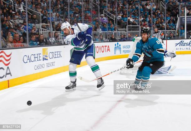 Erik Gudbranson of the Vancouver Canucks clears the puck against Joe Pavelski of the San Jose Sharks at SAP Center on November 11 2017 in San Jose...