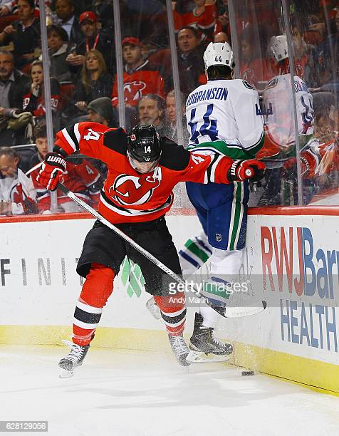 Erik Gudbranson of the Vancouver Canucks is checked into the boards by Adam Henrique of the New Jersey Devils during the game at Prudential Center on...