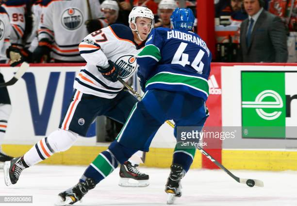 Erik Gudbranson of the Vancouver Canucks looks on as Connor McDavid of the Edmonton Oilers skates up ice with the puck during their NHL game at...