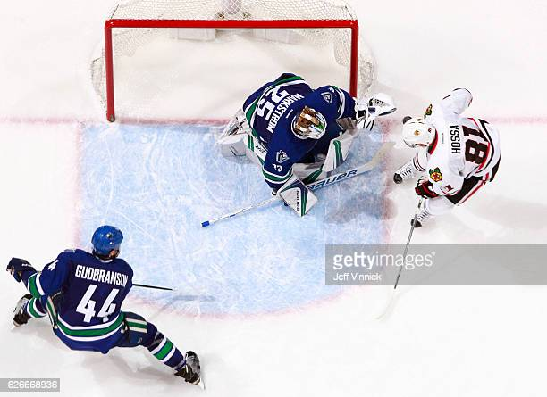 Erik Gudbranson of the Vancouver Canucks looks on as Jacob Markstrom of the Vancouver Canucks makes a save on Marian Hossa of the Chicago Blackhawks...