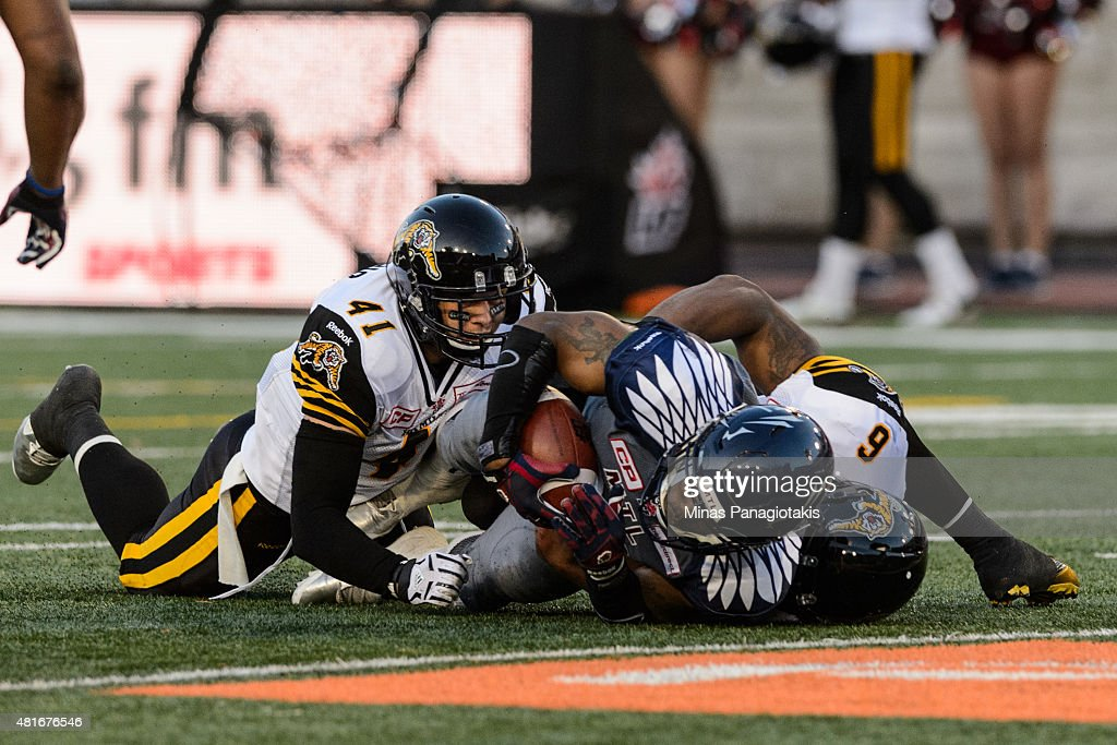 Erik Harris and Bryan Hall of the Hamilton TigerCats hold down Tyrell Sutton of the Montreal Alouettes during the CFL game at Percival Molson Stadium...