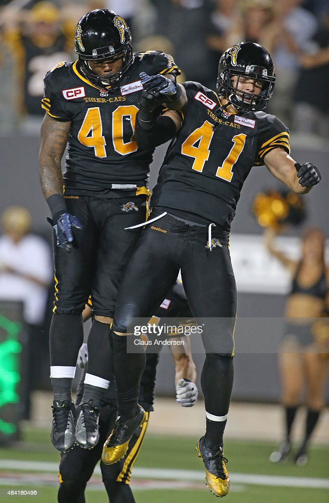 Erik Harris of the Hamilton TigerCats celebrates his touchdown with teammate Eric Norwood against the BC Lions during a CFL football game at Tim...