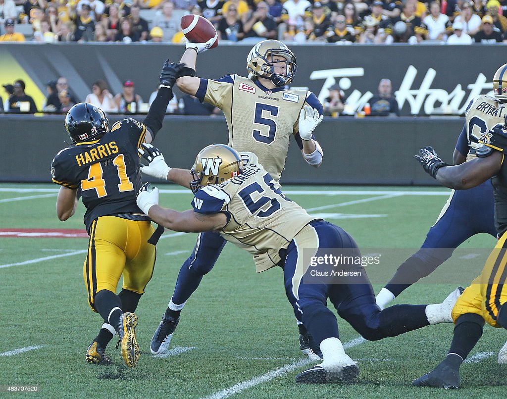 Erik Harris of the Hamilton TigerCats gets a piece of Drew Willy of the Winnipeg Blue Bombers during a CFL football game at Tim Hortons Field on...