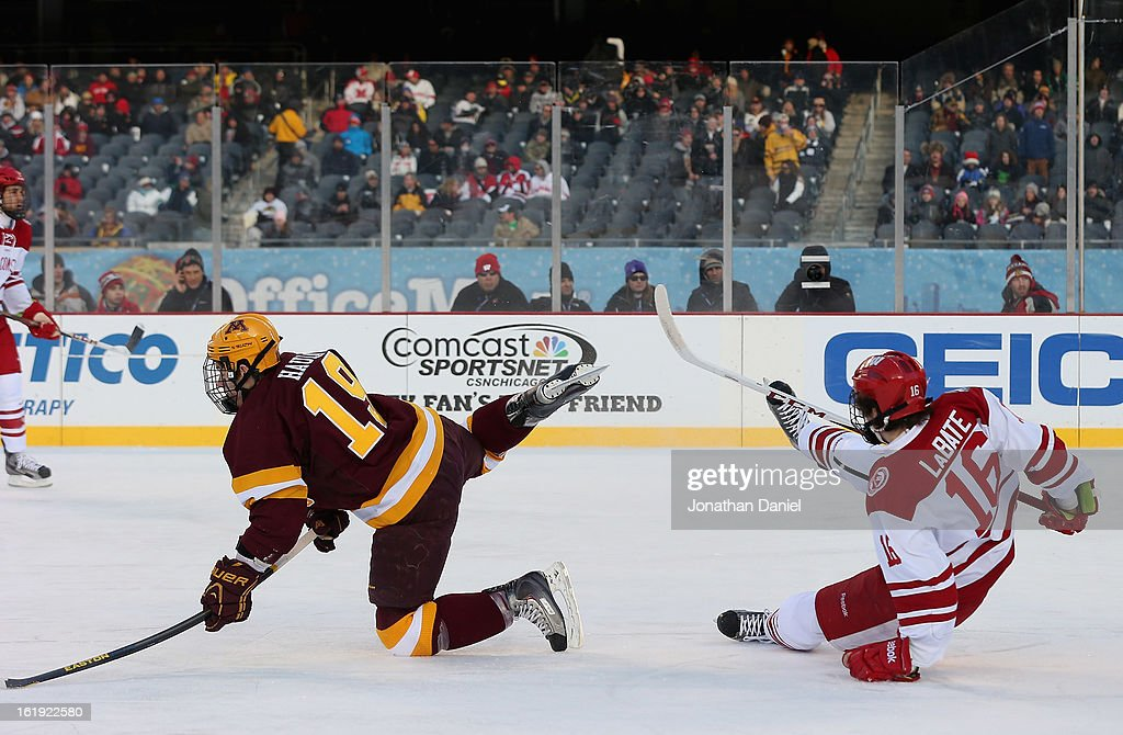 Erik Haula #19 of the Minnesota Golden Gophers collides with Joseph LaBate #16 of the Wisconsin Badgers during the Hockey City Classic at Soldier Field on February 17, 2013 in Chicago, Illinois.