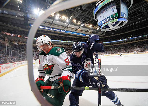Erik Haula of the Minnesota Wild and Jacob Trouba of the Winnipeg Jets battle for the puck along the boards during third period action at the MTS...