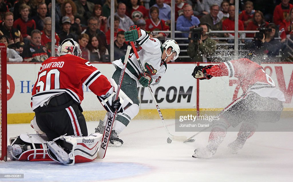 <a gi-track='captionPersonalityLinkClicked' href=/galleries/search?phrase=Erik+Haula&family=editorial&specificpeople=5894652 ng-click='$event.stopPropagation()'>Erik Haula</a> #56 of the Minnesota Wild tries to get off a shot against <a gi-track='captionPersonalityLinkClicked' href=/galleries/search?phrase=Corey+Crawford&family=editorial&specificpeople=818935 ng-click='$event.stopPropagation()'>Corey Crawford</a> #50 and <a gi-track='captionPersonalityLinkClicked' href=/galleries/search?phrase=Nick+Leddy&family=editorial&specificpeople=5894600 ng-click='$event.stopPropagation()'>Nick Leddy</a> #8 of the Chicago Blackhawks in Game One of the Second Round of the 2014 NHL Stanley Cup Playoffs at the United Center on May 2, 2014 in Chicago, Illinois. The Blackhawks defeated the Wild 5-2.