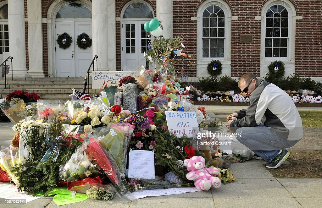 Erik Johannsen of Dover, Maryland, places stuffed animals at a memorial Monday, December 24, 2012, to honor the 26 people killed in the Sandy Hook Elementary School shooting in Newtown, Connecticut. Johannsen, a member of the Air Force in Dover and a volunteer firefighter, stopped to pay his respects on his way to be with family in New Hampshire.