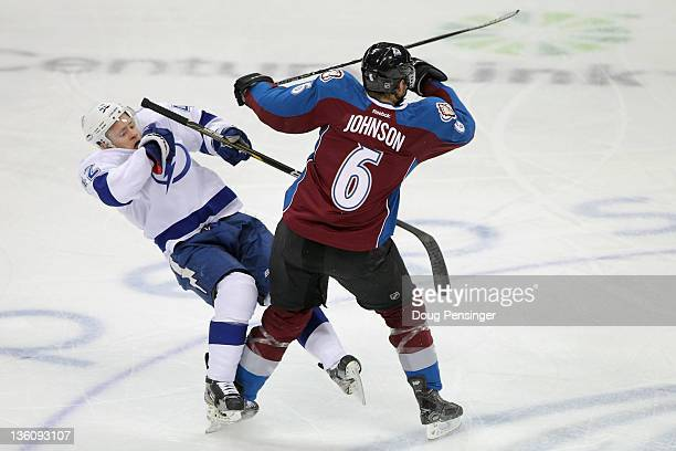 Erik Johnson of the Colorado Avalanche delivers a hit to Dana Tyrell of the Tampa Bay Lightning at the Pepsi Center on December 23 2011 in Denver...