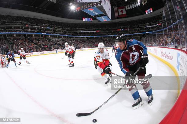 Erik Johnson of the Colorado Avalanche skates Nikolaj Ehlers of the Calgary Flames at the Pepsi Center on November 25 2017 in Denver Colorado The...