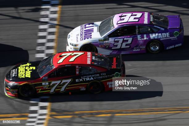 Erik Jones driver of the 5hour Energy Extra Strength Toyota races Matt DiBenedetto driver of the EJ Wade Construction Ford during the 59th Annual...