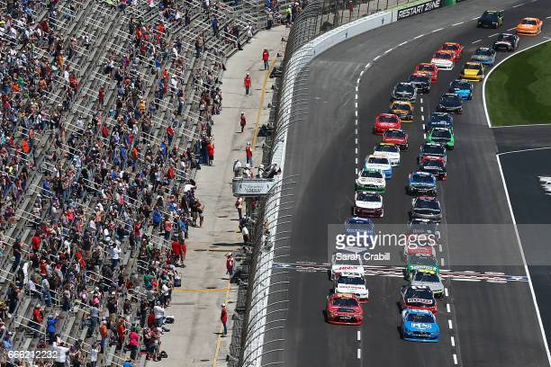 Erik Jones driver of the GameStop/GAEMS Toyota and Joey Logano driver of the PPG Ford lead the field past the green flag to start the NASCAR XFINITY...