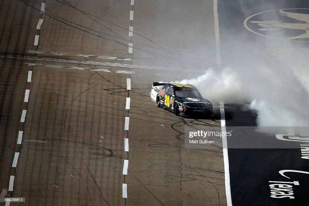 Erik Jones driver of the GameStop/Mortal Kombat X Toyota celebrates with a burnout after winning the NASCAR XFINITY Series O'Reilly Auto Parts 300 at...