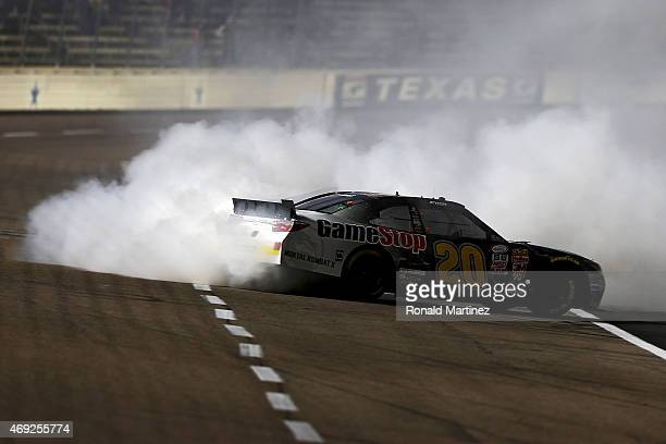 Erik Jones driver of the GameStop/Mortal Kombat X Toyota celebrates with a burnout after winning during the NASCAR XFINITY Series O'Reilly Auto Parts...