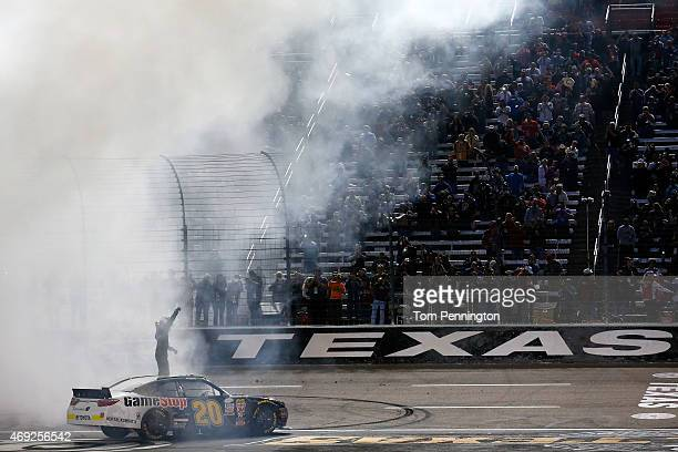 Erik Jones driver of the GameStop/Mortal Kombat X Toyota celebrates by saluting the crowd after a burnout after winning the NASCAR XFINITY Series...