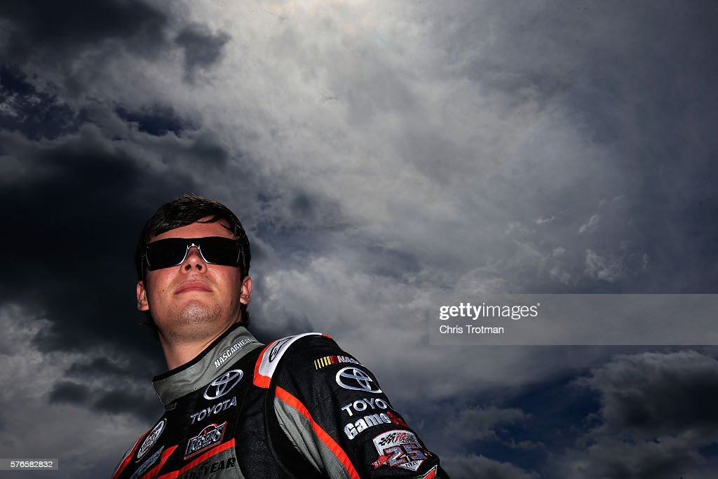 Erik Jones driver of the GameStop/NASCAR Heat Evolution Toyota stands on the grid during qualifying for the NASCAR XFINITY Series AutoLotto 200 at...