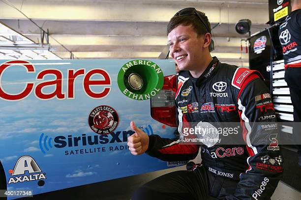 Erik Jones driver of the Hiring Our Heroes/ToyotaCare Toyota poses by a logo on his truck bearing his high school's name and mascot in the garage...