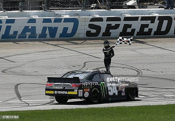 Erik Jones driver of the Monster Energy Toyota waves the checkered flag after winning the NASCAR XFINITY Owens Corning AttiCat 300 at Chicagoland...