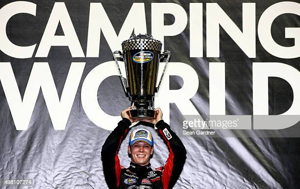 Erik Jones driver of the Toyota celebrates with the trophy in Victory Lane after winning the series championship during the NASCAR Camping World...