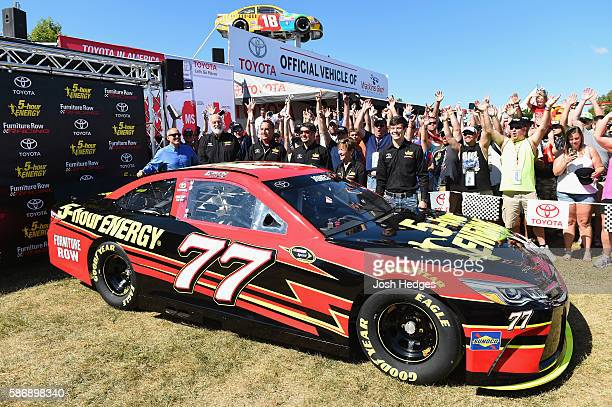 Erik Jones Martin Truex Jr driver of the Furniture Row Toyota and team owner Barney Visser pose with the 5hour Energy Toyota that Jones will drive in...