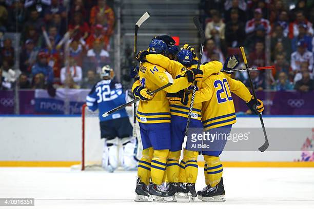 Erik Karlsson of Sweden celebrates his goal with teammates after scoring in the second period against Kari Lehtonen of Finland during the Men's Ice...