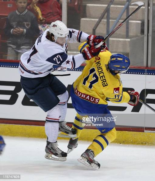 Erik Karlsson of Team Sweden is hit by Adam Erne of Team USA during the 2013 USA Hockey Junior Evaluation Camp at the Lake Placid Olympic Center on...