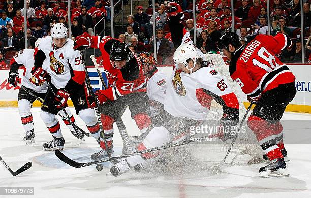 Erik Karlsson of the Ottawa Senators and Mattias Tedenby of the New Jersey Devils battle hard for the puck during the game at the Prudential Center...