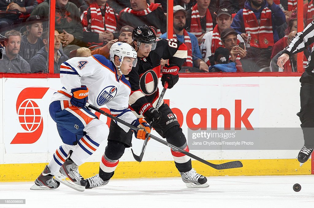 <a gi-track='captionPersonalityLinkClicked' href=/galleries/search?phrase=Erik+Karlsson&family=editorial&specificpeople=5370939 ng-click='$event.stopPropagation()'>Erik Karlsson</a> #65 of the Ottawa Senators battles against <a gi-track='captionPersonalityLinkClicked' href=/galleries/search?phrase=Taylor+Hall&family=editorial&specificpeople=2808377 ng-click='$event.stopPropagation()'>Taylor Hall</a> #4 of the Edmonton Oilers for the puck during an NHL game at Canadian Tire Centre on October 19, 2013 in Ottawa, Ontario, Canada.