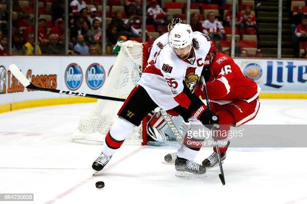 Erik Karlsson of the Ottawa Senators battles for the puck with Ben Street of the Detroit Red Wings during the first period at Joe Louis Arena on...