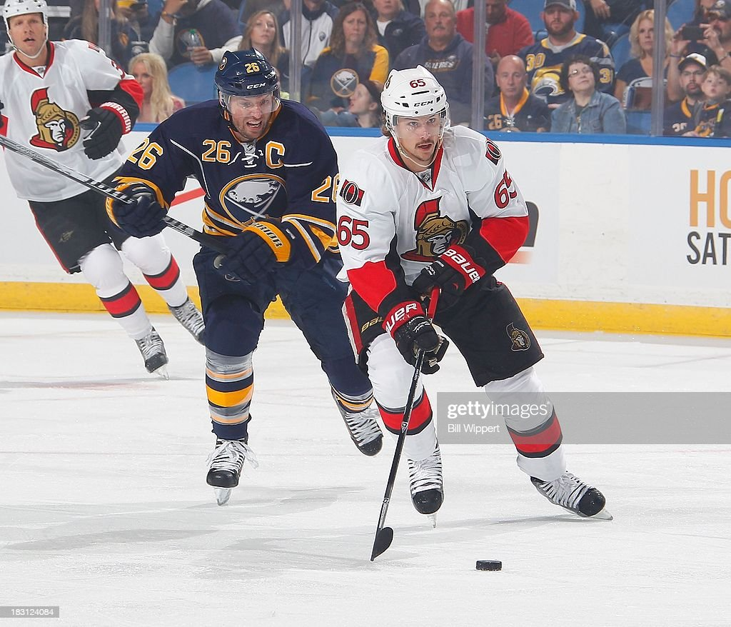 Erik Karlsson #65 of the Ottawa Senators carries the puck, trailed by Thomas Vanek #26 of the Buffalo Sabres on October 4, 2013 in the home opener at the First Niagara Center in Buffalo, New York.