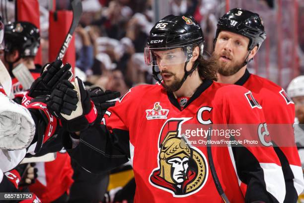 Erik Karlsson of the Ottawa Senators celebrates a first period goal by teammate Derick Brassard with Marc Methot against the Pittsburgh Penguins in...