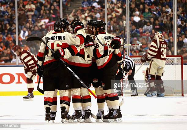 Erik Karlsson of the Ottawa Senators celebrates his goal with teammates during the first period of the 2014 Tim Hortons NHL Heritage Classic game...