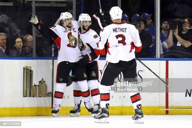 Erik Karlsson of the Ottawa Senators celebrates with teammates Derick Brassard and Marc Methot after scoring a goal against Henrik Lundqvist of the...