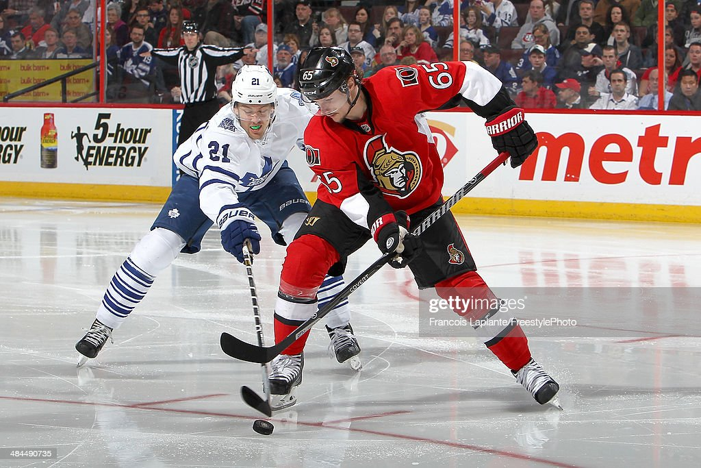 Erik Karlsson #65 of the Ottawa Senators controls the puck against James van Riemsdyk #21 of the Toronto Maple Leafs on April 12, 2014 at Canadian Tire Centre in Ottawa, Ontario, Canada.
