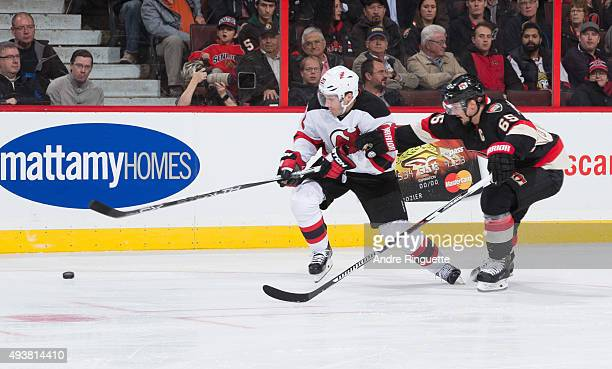 Erik Karlsson of the Ottawa Senators defends against Lee Stempniak of the New Jersey Devils at Canadian Tire Centre on October 22 2015 in Ottawa...