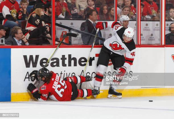 Erik Karlsson of the Ottawa Senators falls into the boards after a collision with Blake Coleman of the New Jersey Devils at Canadian Tire Centre on...