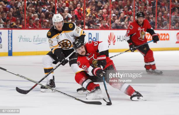 Erik Karlsson of the Ottawa Senators falls to the ice while making a sharp turn with the puck as Riley Nash of the Boston Bruins defends against in...