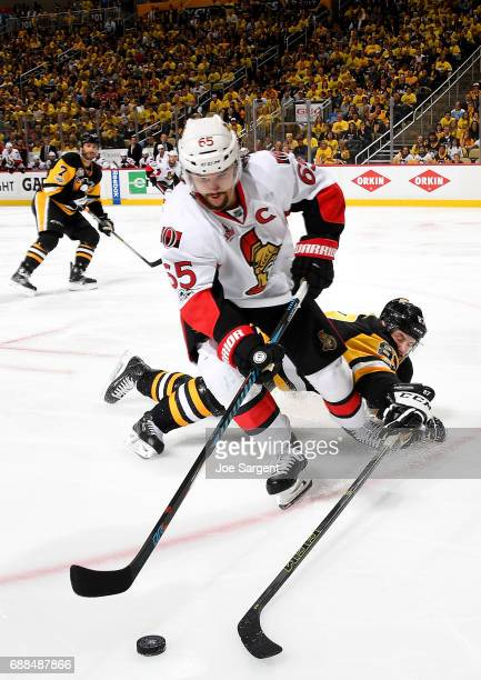 Erik Karlsson of the Ottawa Senators handles the puck against Sidney Crosby of the Pittsburgh Penguins in Game Seven of the Eastern Conference Final...