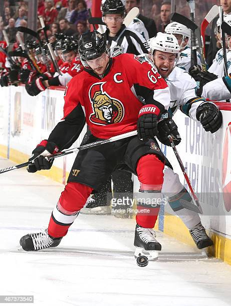 Erik Karlsson of the Ottawa Senators muscles Barclay Goodrow of the San Jose Sharks off the puck along the boards at Canadian Tire Centre on March 23...