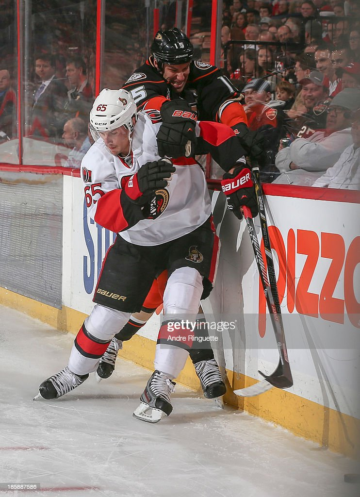 <a gi-track='captionPersonalityLinkClicked' href=/galleries/search?phrase=Erik+Karlsson&family=editorial&specificpeople=5370939 ng-click='$event.stopPropagation()'>Erik Karlsson</a> #65 of the Ottawa Senators pins <a gi-track='captionPersonalityLinkClicked' href=/galleries/search?phrase=Ryan+Getzlaf&family=editorial&specificpeople=602655 ng-click='$event.stopPropagation()'>Ryan Getzlaf</a> #15 of the Anaheim Ducks against the boards at Canadian Tire Centre on October 25, 2013 in Ottawa, Ontario, Canada.