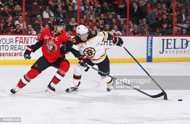 Erik Karlsson of the Ottawa Senators reaches with his stick to pokecheck the puck off David Pastrnak of the Boston Bruins at Canadian Tire Centre on...