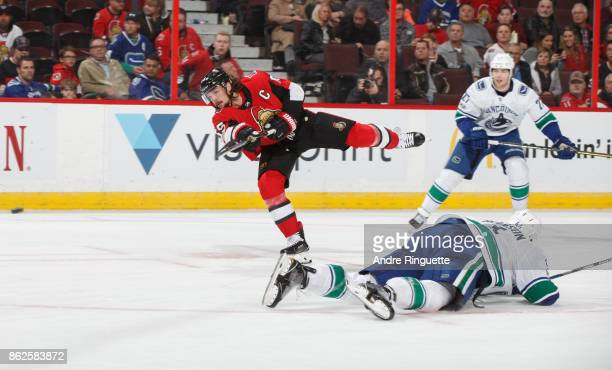 Erik Karlsson of the Ottawa Senators shoots the puck against Erik Gudbranson and Ben Hutton of the Vancouver Canucks at Canadian Tire Centre on...
